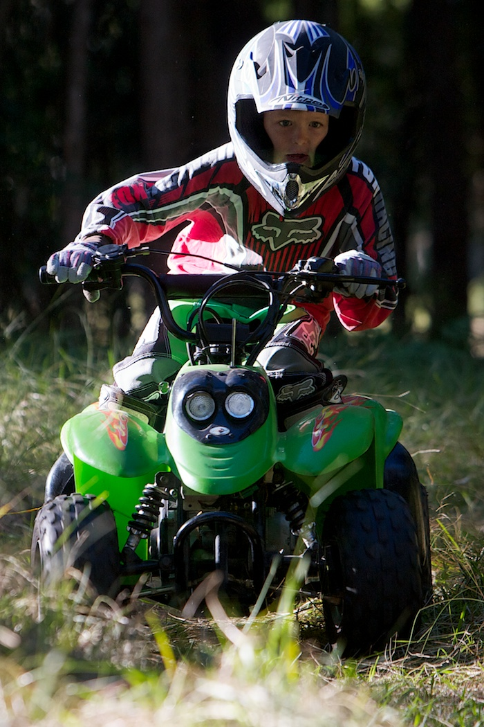Sport/action photo of child riding an ATV quad bike.
