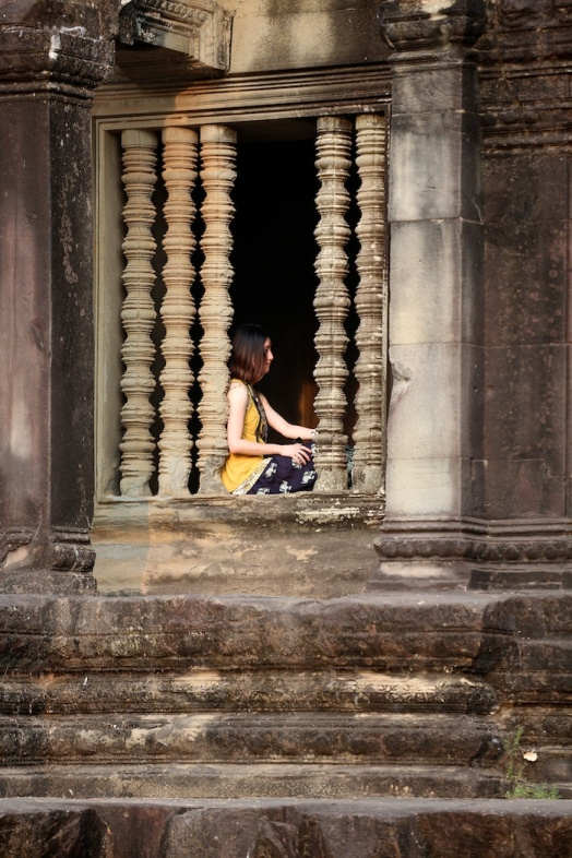 A young lady poses for someone else at Angkor Wat, Cambodia